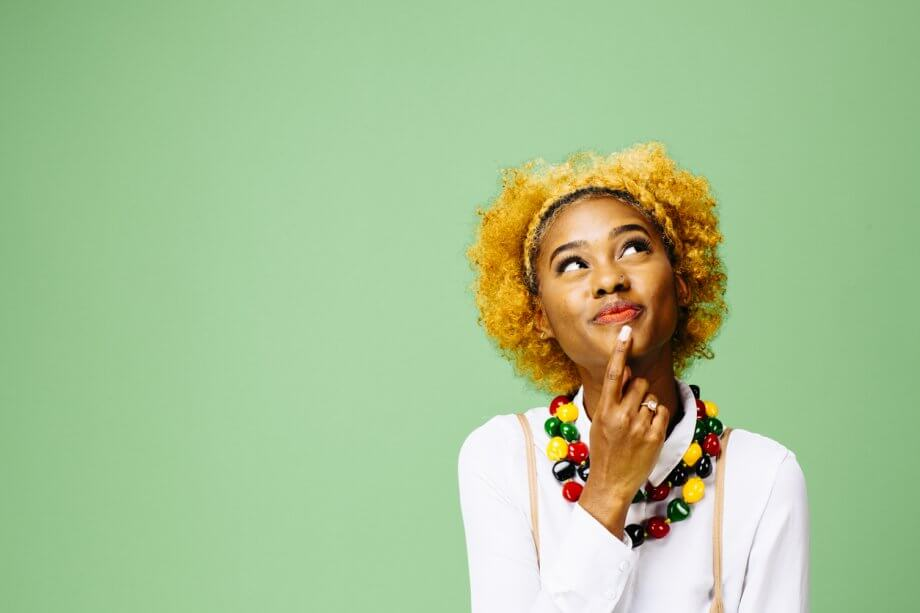 Woman with short curly blonde hair looking up happily while thinking about something in front of a green background.
