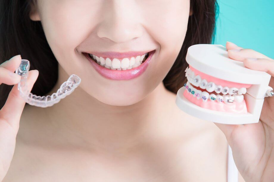 girl holding invisalign and model of braces in hands