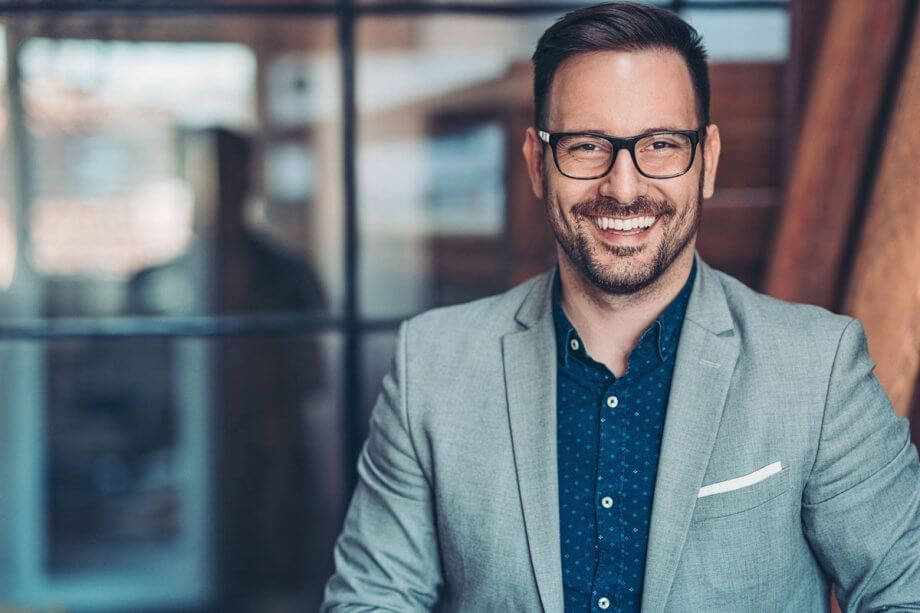 man with beard and glasses, dressed business casual, smiling
